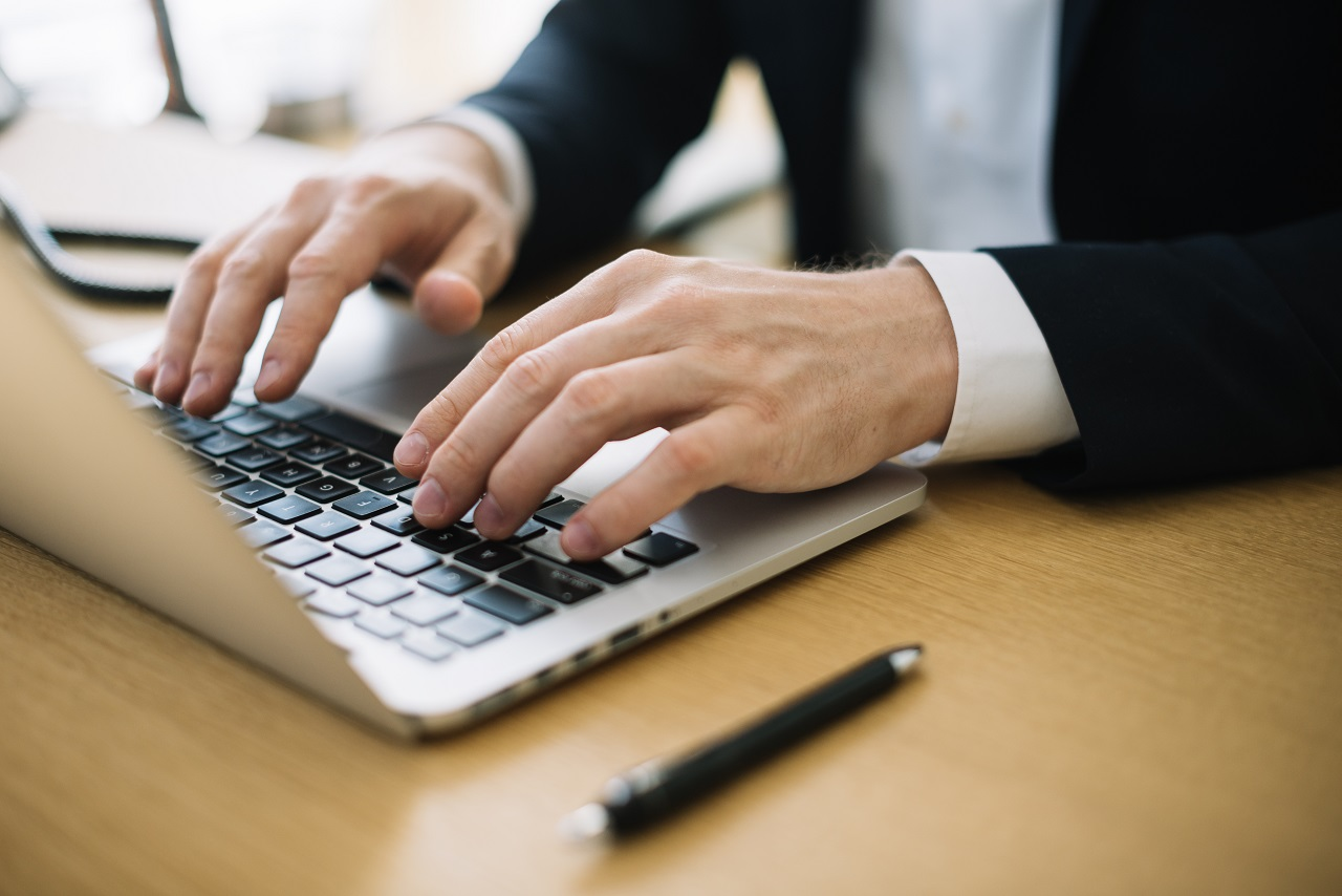 Close up of a businessman typing on a laptop
