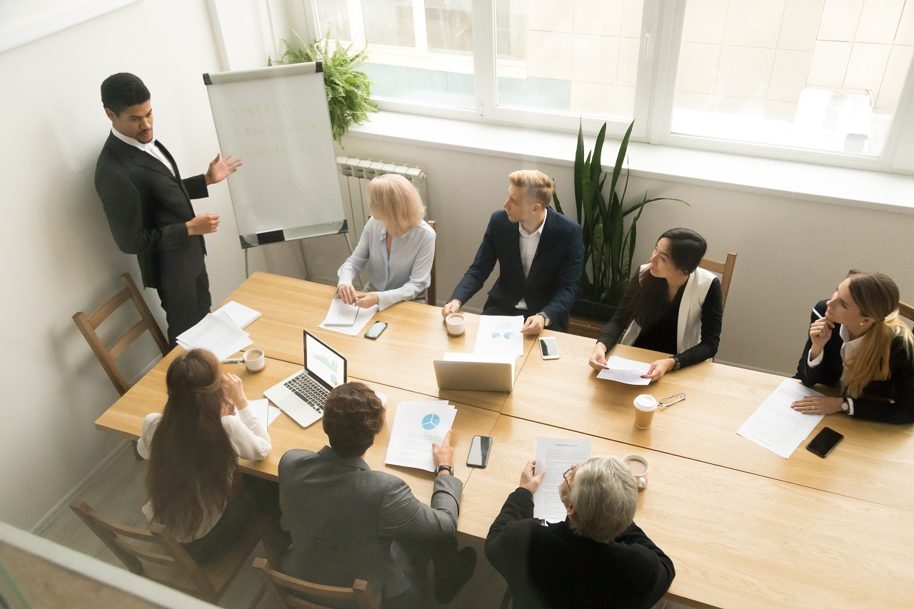 A businessman presenting to a room of his officemates