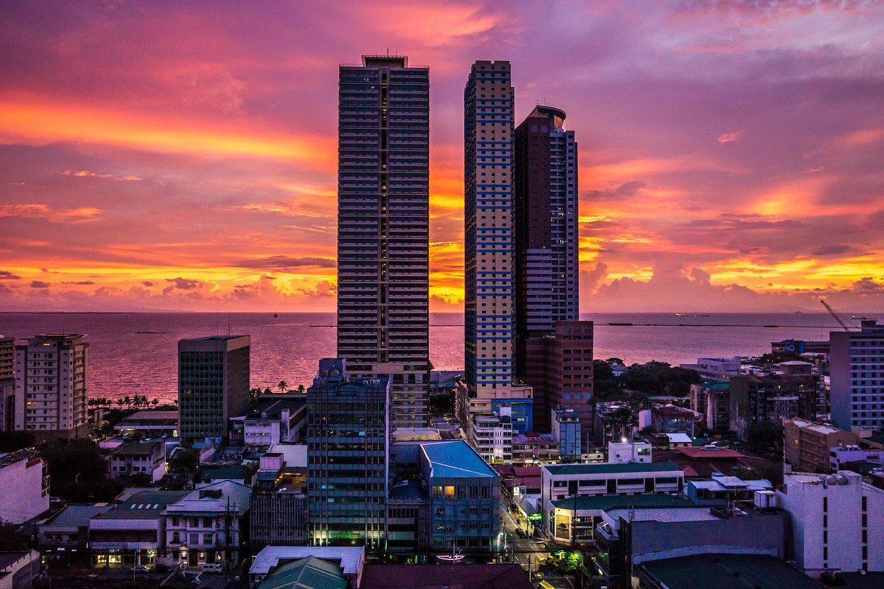 Buildings in Manila with the sun setting behind it