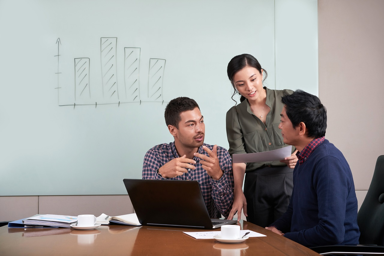 Two asian coworkers finalizing meeting discussions with their boss