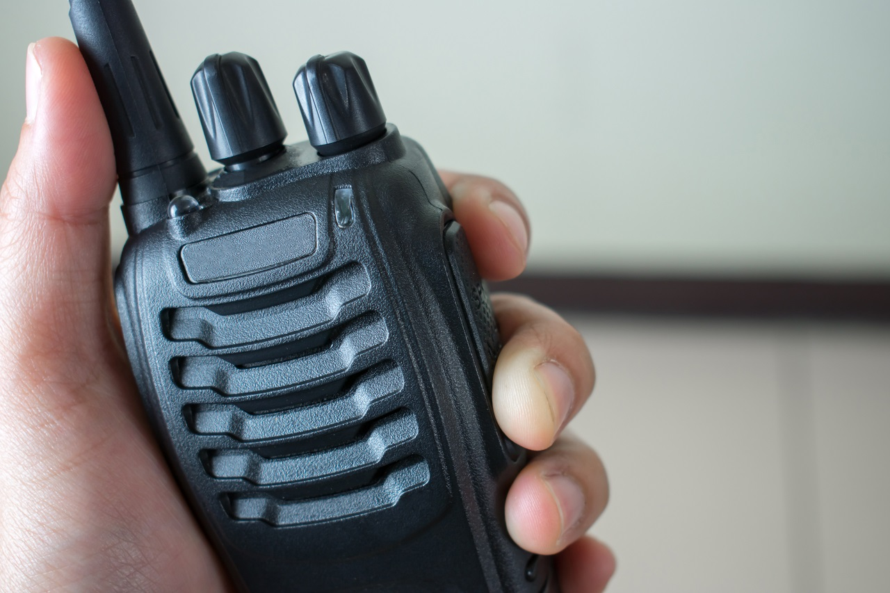 A hand holding a walkie talkie