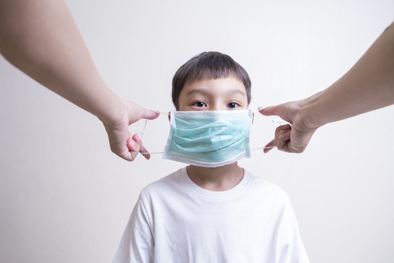 A parent putting a face mask on their child