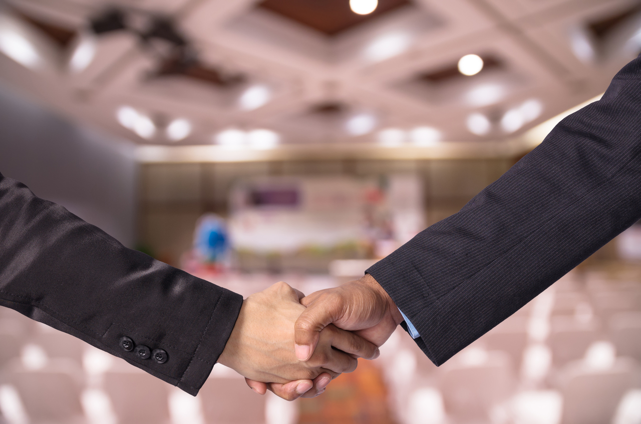 A businessman and a newly hired employee shaking hands