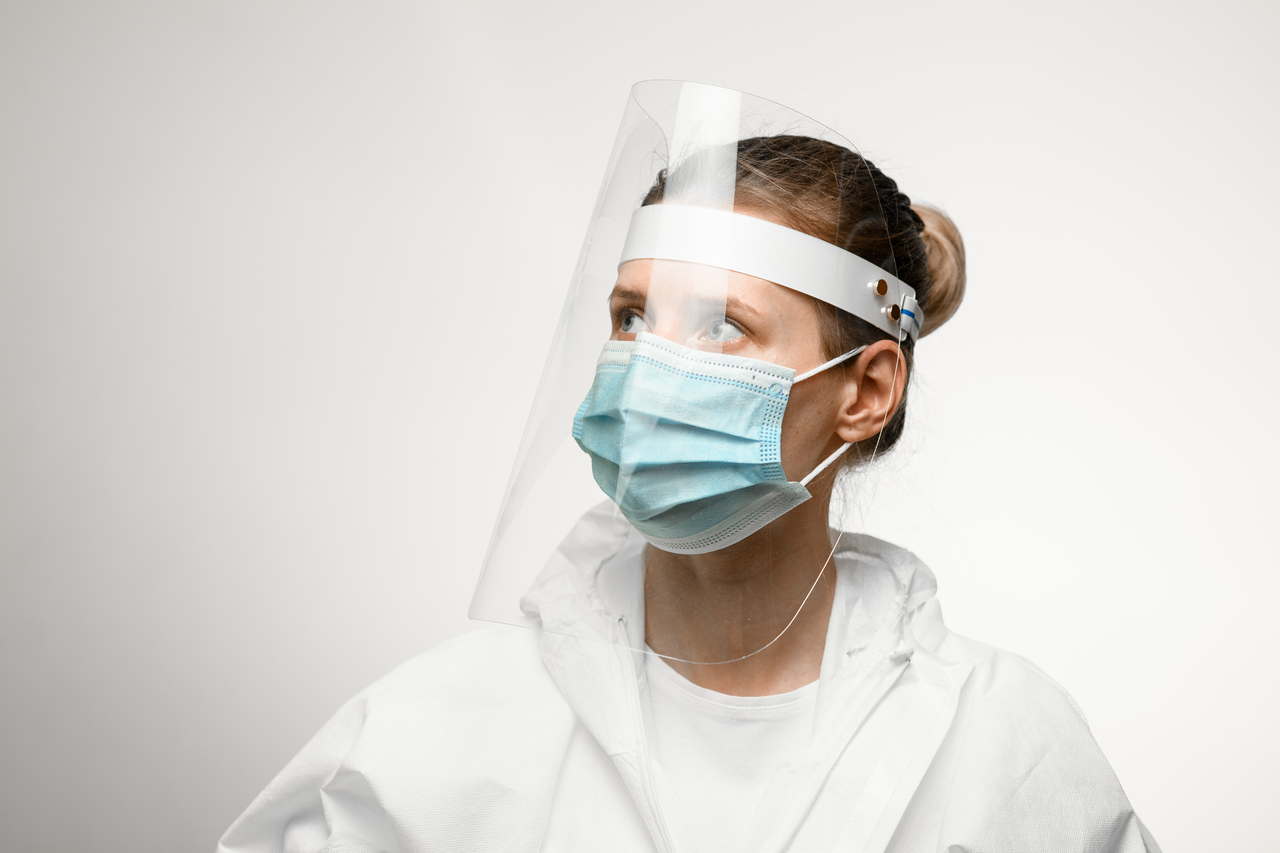 A medical professional with a face shield on